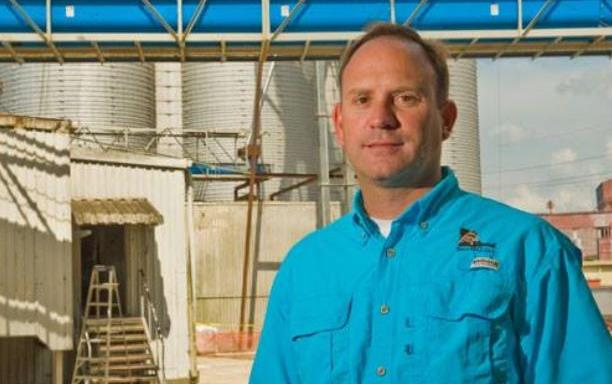 White man wearing blue shirt stands in front of rice mill
