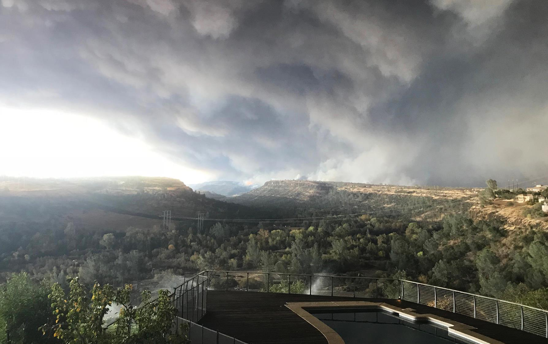 CA Camp Fire, Logan Wilson photo, mass of smoke covers the whole sky above mountains (background) and tree-filled valley (foreground)