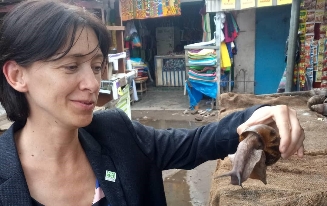 Woman wearing black blazer with Think Rice lapel pin visits an outdoor food market and holds gigantic snail