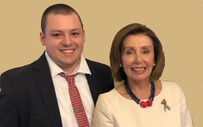Intern Grant Long, wearing suit and tie, stands next to Speaker of the House Nancy Pelosi, wearing white dress, carrying small brown bag
