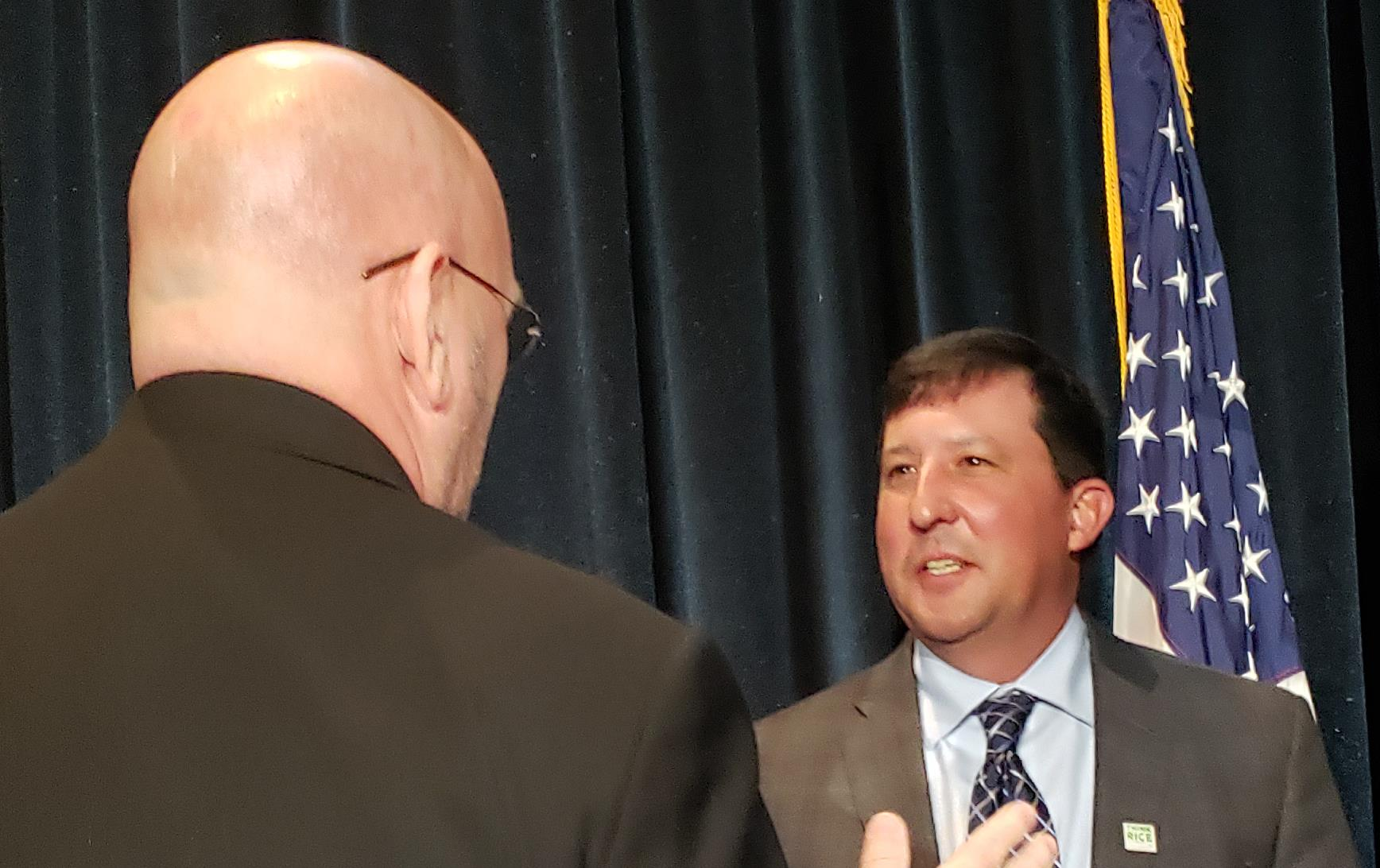 Two white men wearing business suits engaged in animated conversation, American flag in background
