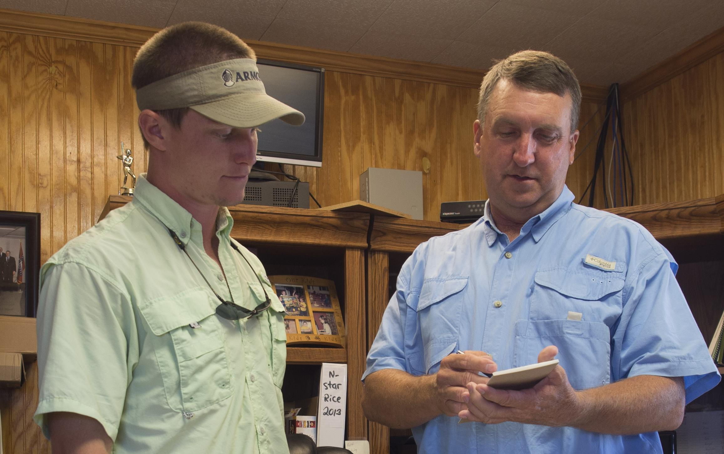 Two men dressed in casual shirts and pants stand next to desk in wood paneled office, checking details on a pad of paper