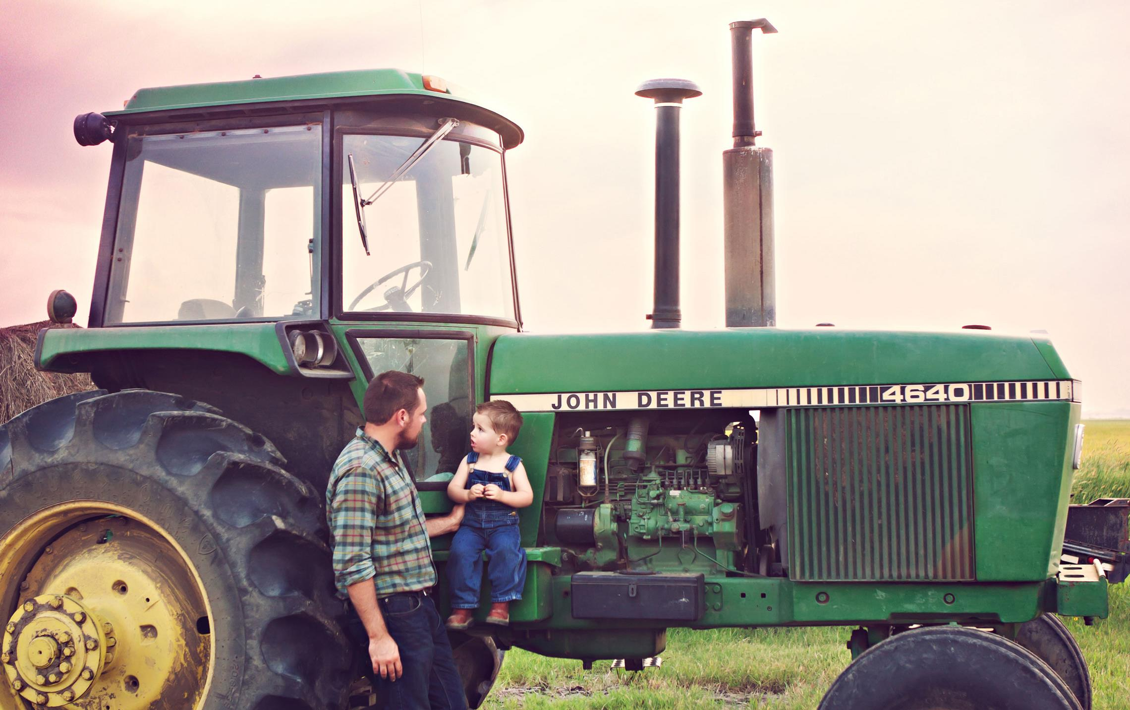 Father holds son wearing overalls up against vintage John Deere tractor