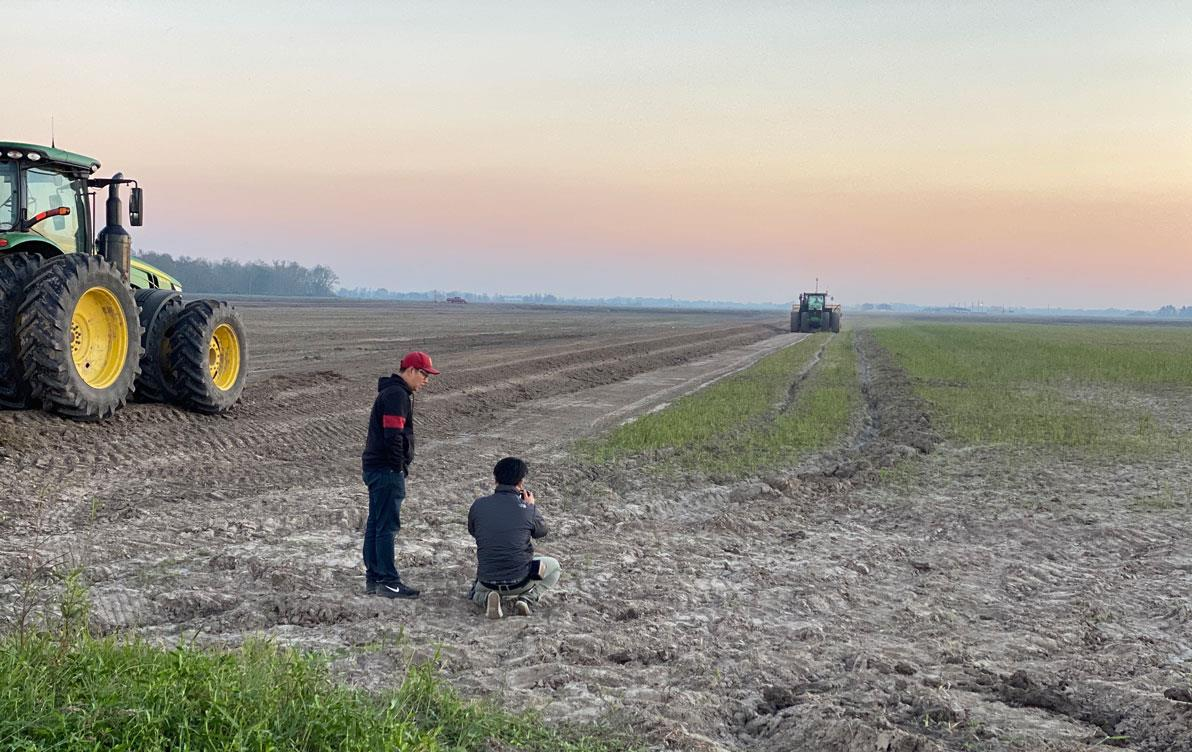Tow men film combines on a barren field at sunset