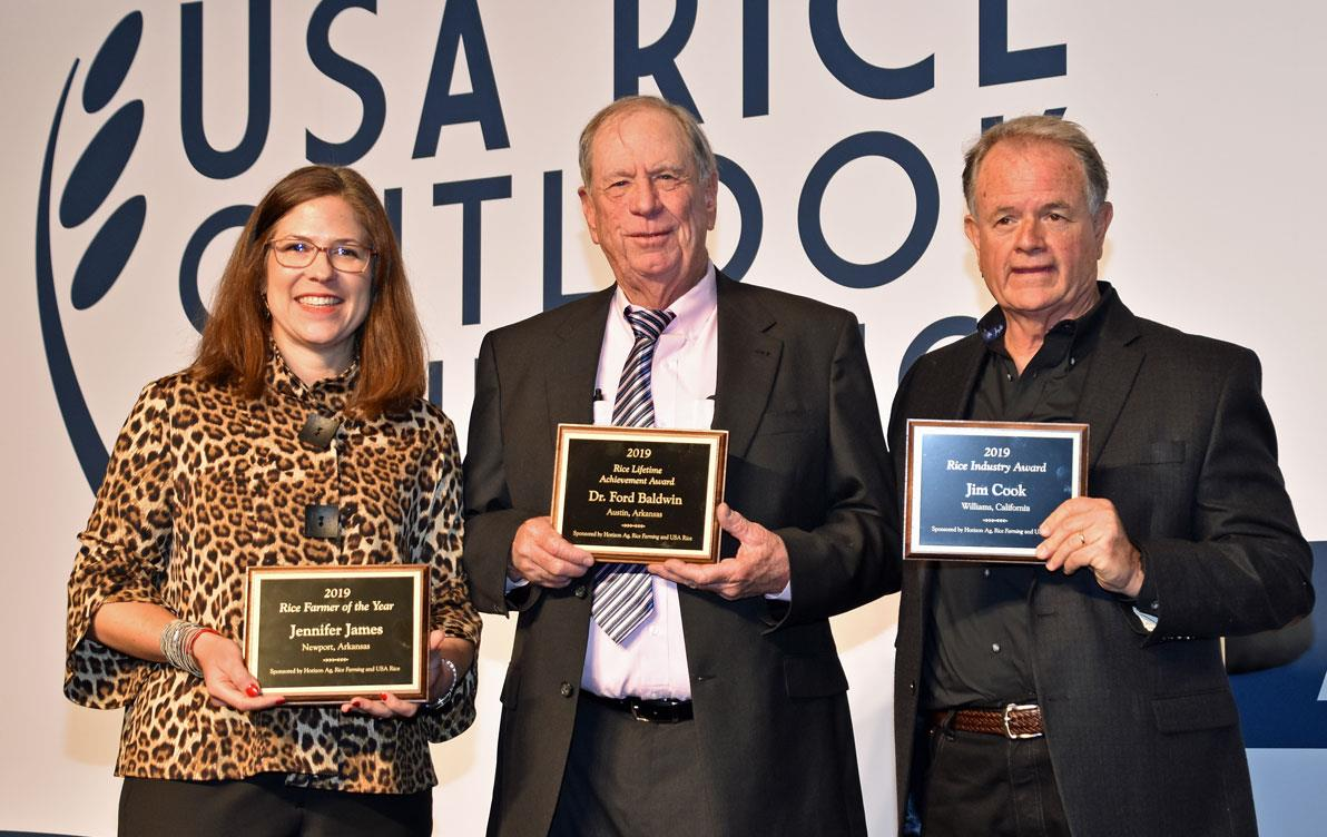 A woman and two men stand together holding awards plaques