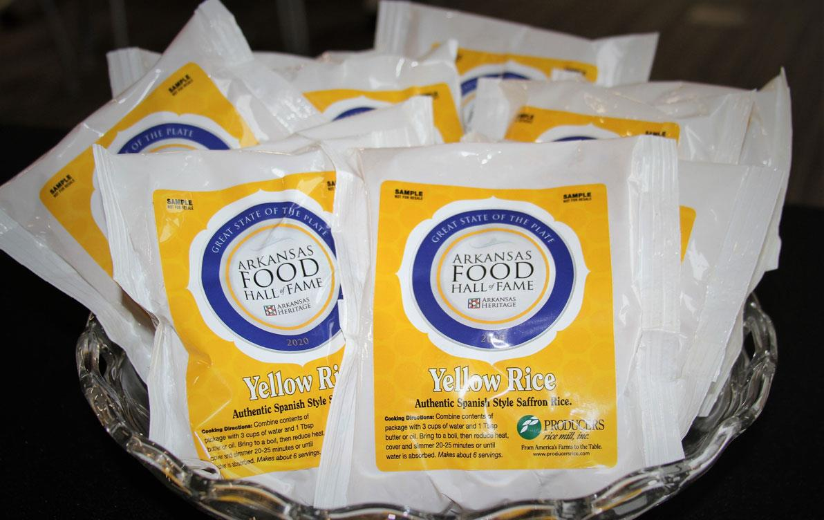 "Bags of rice with colorful yellow & blue labels saying ""Arkansas Food Hall of Fame"""
