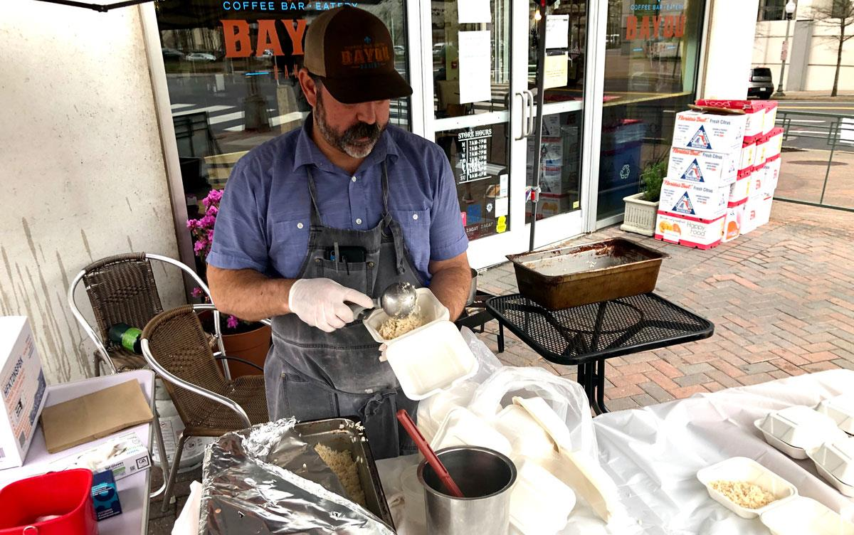Man wearing apron and ballcap serves rice at catering table on sidewalk outside Bayou Bakery