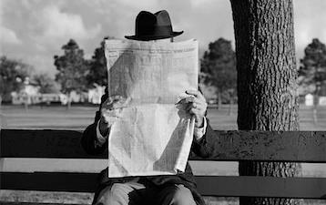 Black & white photo of man wearing a top hat, sitting on bench reading newspaper