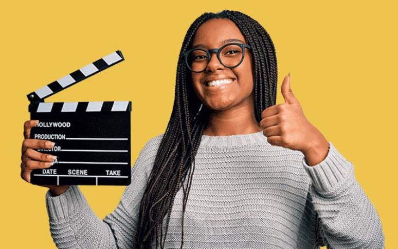 Young, black female student holds movie clapboard and does thumbs up, yellow bkgd