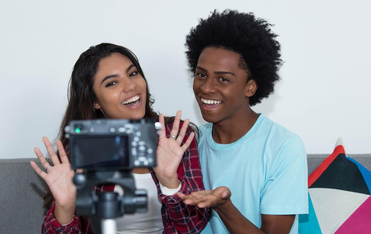Two students sit on couch in front of camera-on-tripod