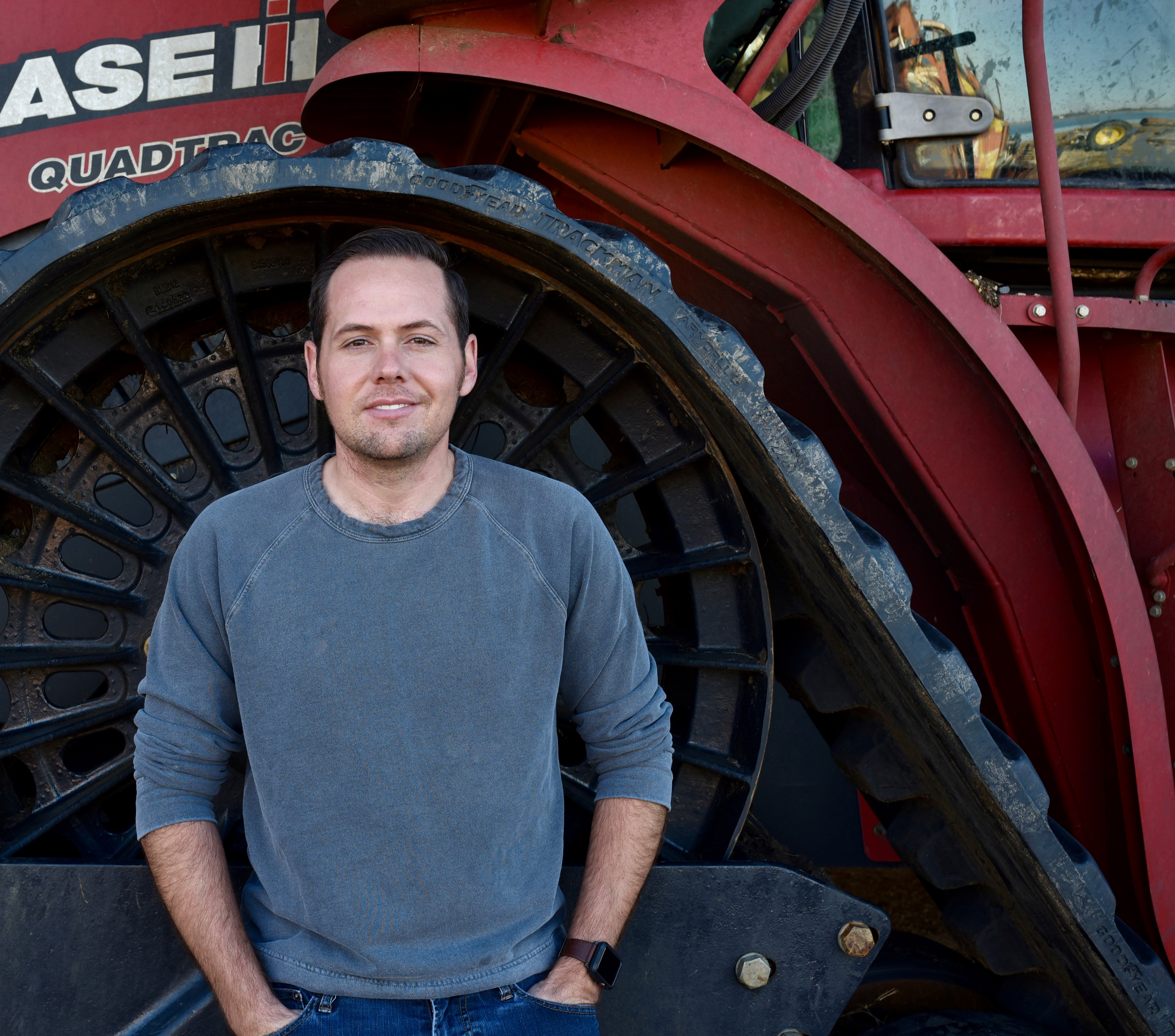 Young white male wearing gray sweatshirt standing in wheel well of Case combine