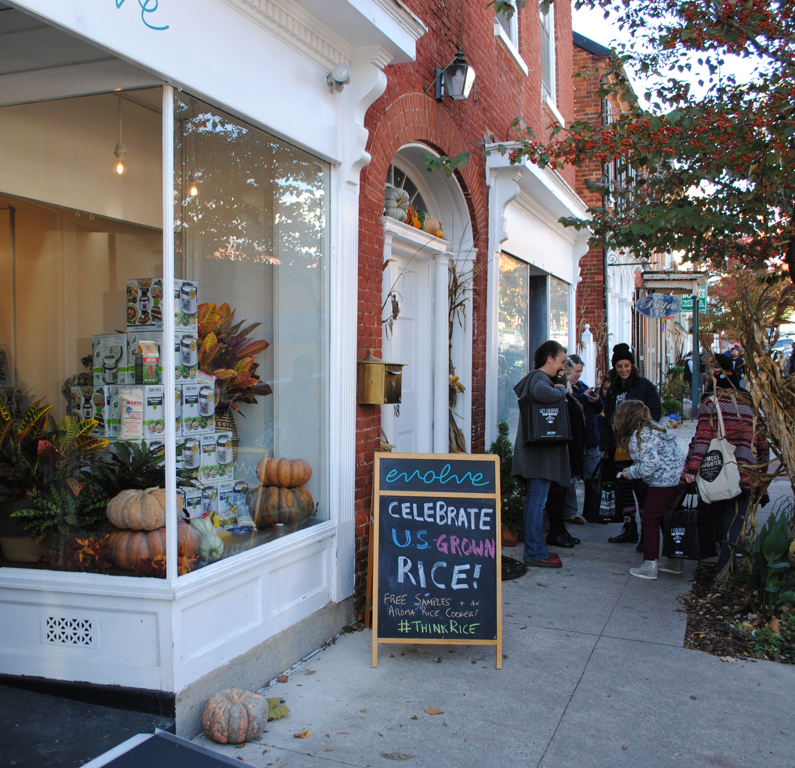Sign outside storefront reads: Celebrate U.S. Grown Rice! Stack of rice cookers and pumpkins in store window, people standing outside on sidewalk