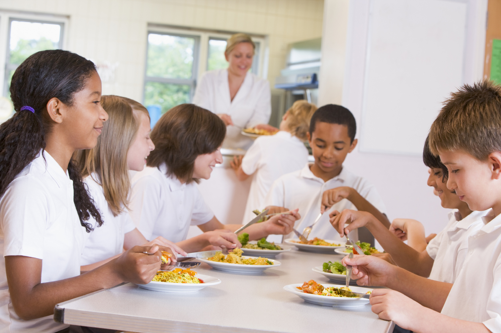 Group of students eat lunch at cafeteria table