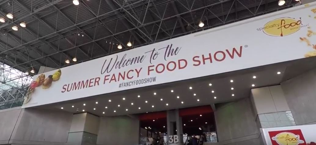2018 Fancy Food Show welcome signage hanging from ceiling in convention center