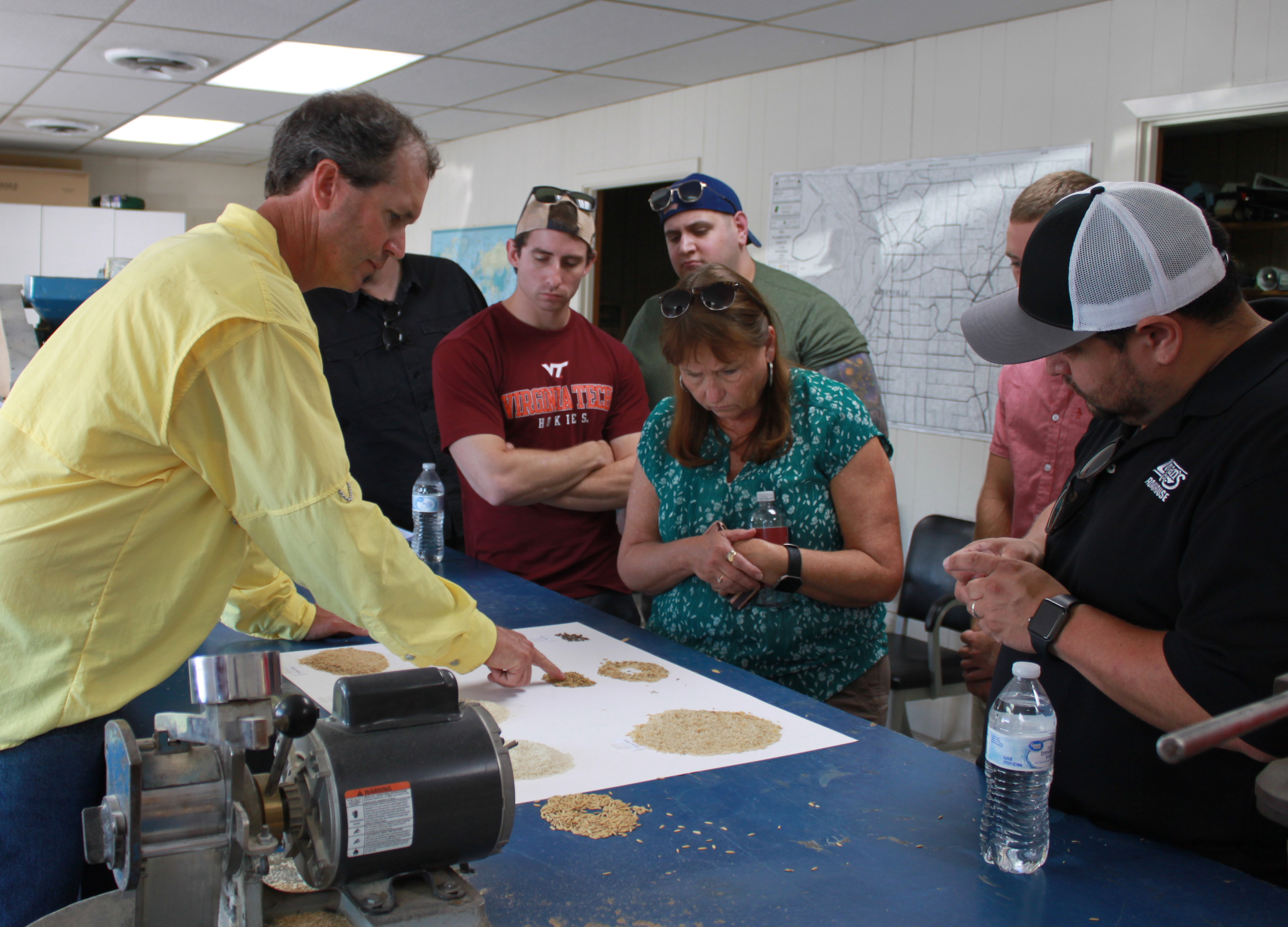 People gathered around blue-topped table for milling demo