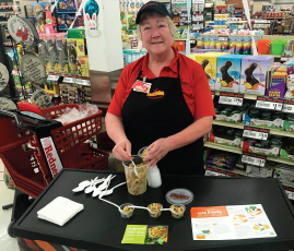 Woman wearing apron and ballcap hands out rice samples at a grocery store, red grocery cart at her side