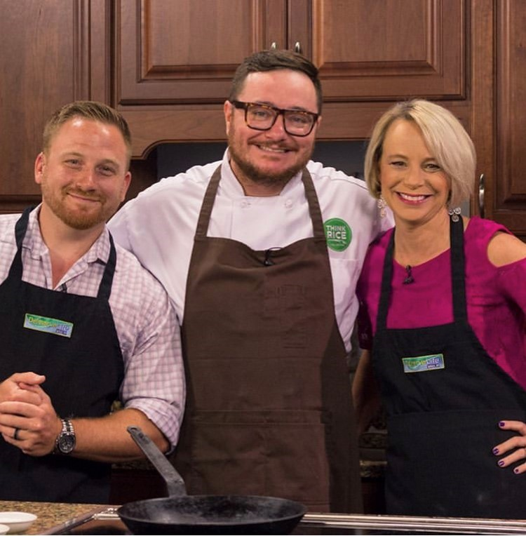 Chef Hari Cameron wearing Think Rice chef coat and brown apron stands with his arms around a man and a woman wearing black aprons