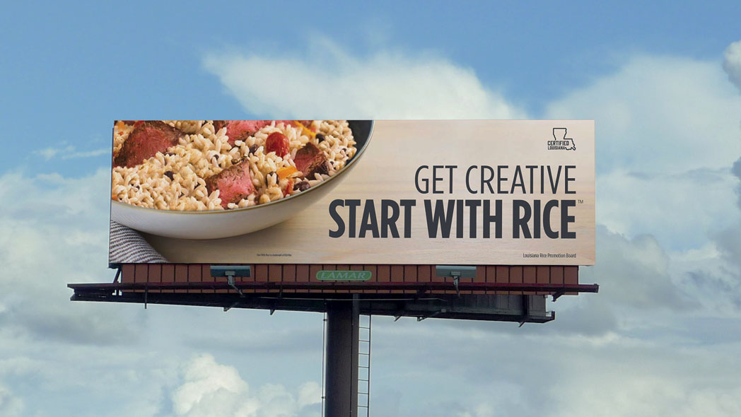 """Billboard with bowl of rice and meat w/text """"Get Creative Start With Rice"""" against blue sky & white clouds"""