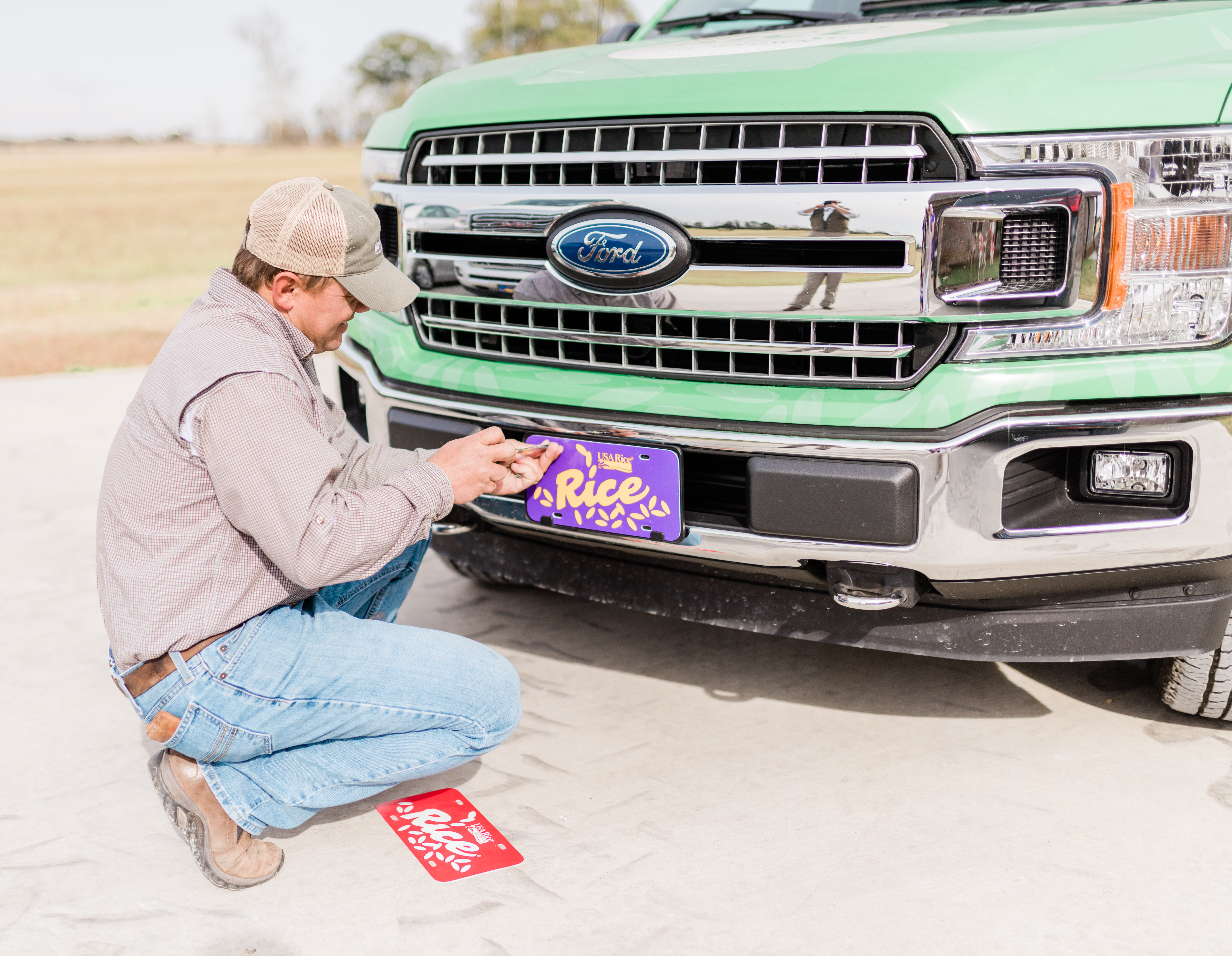 Man kneeling in front of Rice Truck, changing license plate from red to purple