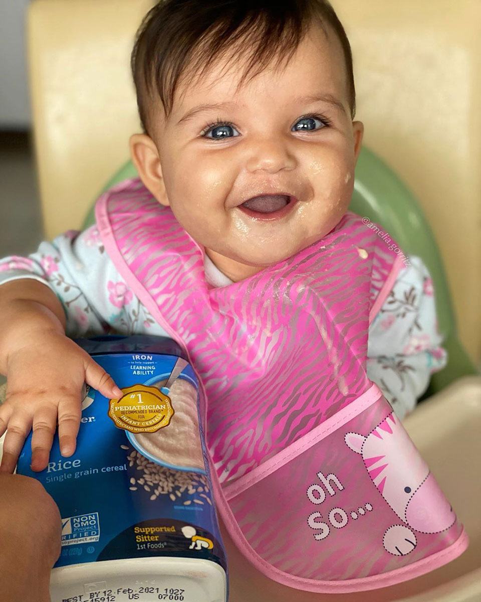 Smiling baby in high chair wearing pink bib with hand on package of infant rice cereal