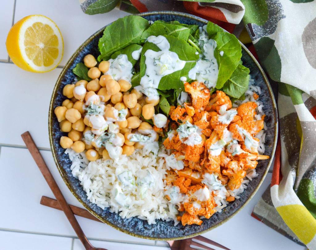 Blue bowl filled with rice, chickpeas, roasted cauliflower and spinach