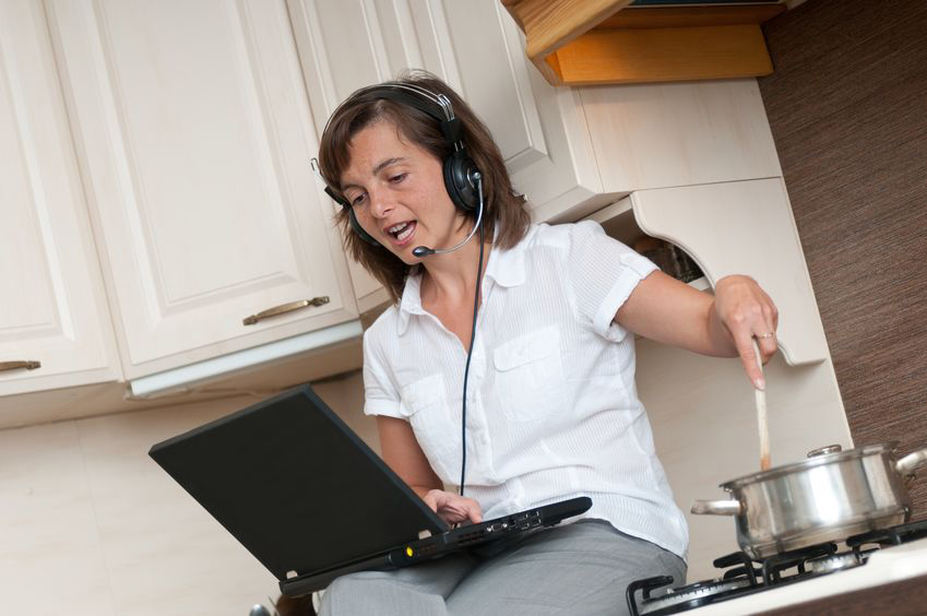 Woman sits on kitchen counter, cooking and working on computer
