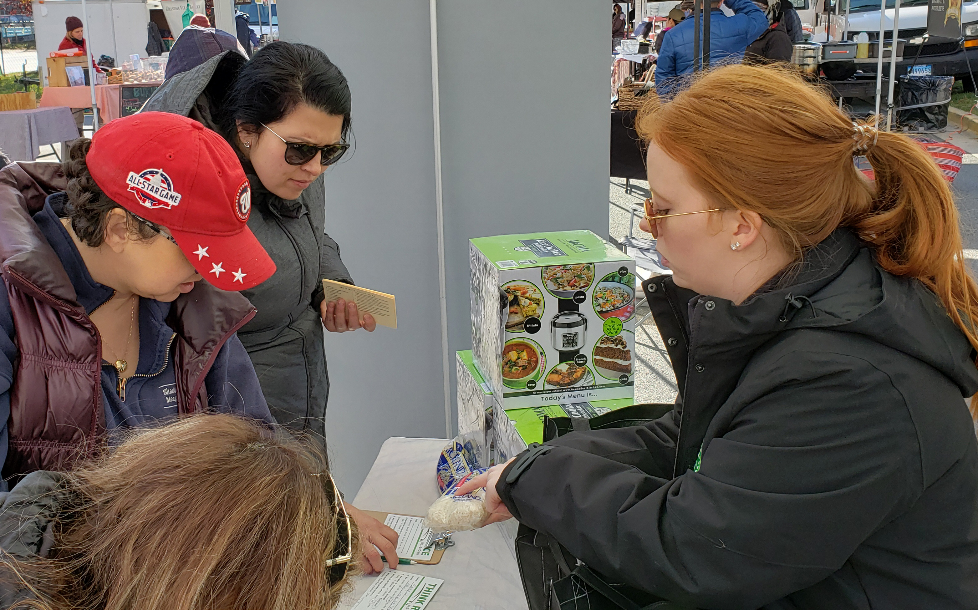 Red-haired woman points out label on bag of rice to people standing in front of table holding rice cookers