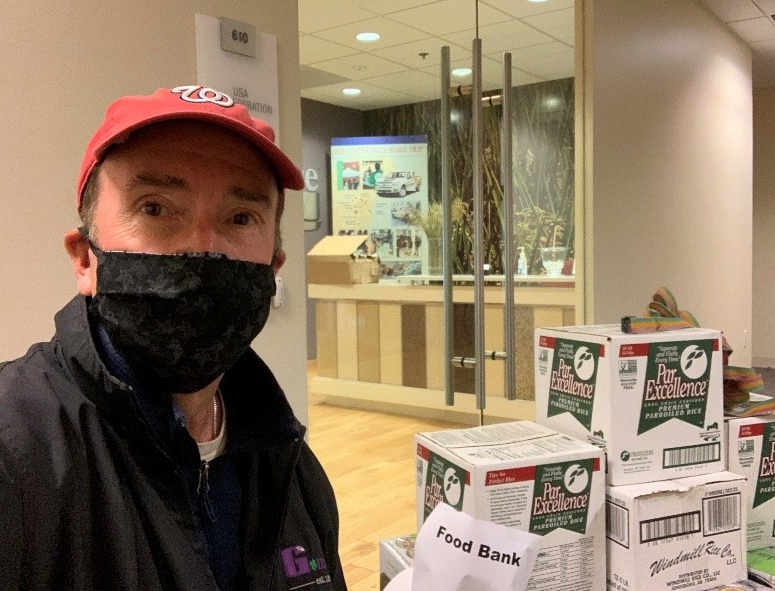 White man wearing Nationals ballcap and black face mask stands next to rice boxes for food bank donation