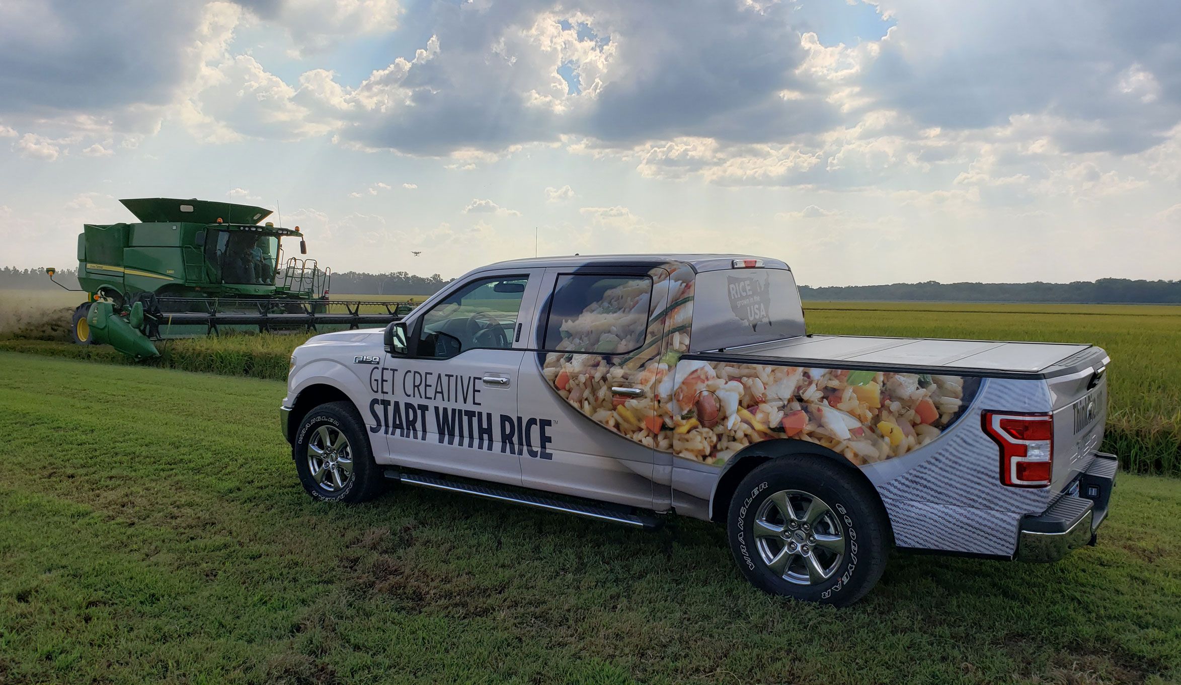 2019 Think Rice Truck sits in rice field in front of green combine, sun shining through clouds