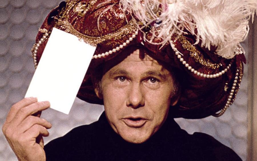 Johnny Carson as Carnac the Magnificent wearing jeweled turban, holding envelope in one hand