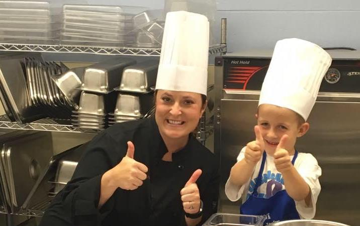 Woman and young boy wearing toques give the thumbs up sign