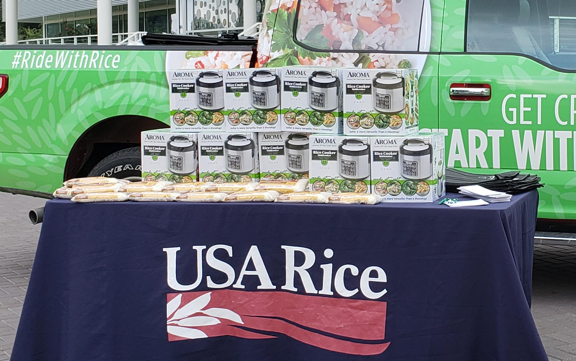 """Green pickup truck with designs & words """"Get Creative, Start With Rice,"""" sits behind table with USA Rice banner and stacks of boxes on top"""