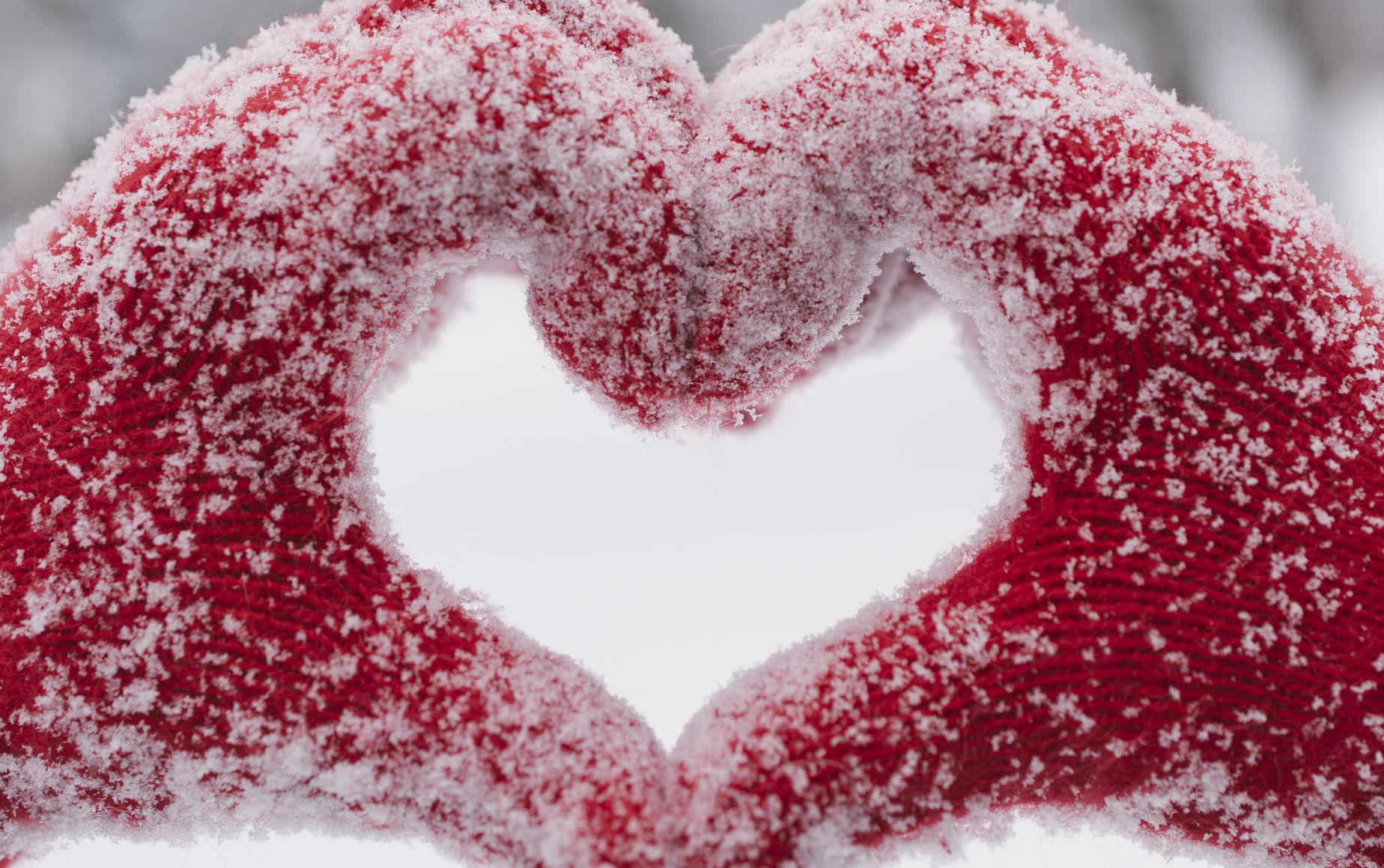 Hands wearing red mittens form a heart covered with snow