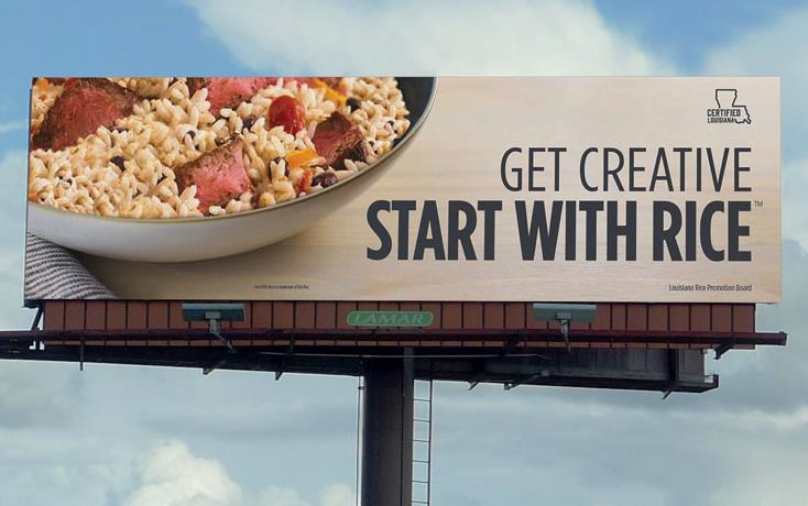 "Billboard with bowl of rice and meat w/text ""Get Creative Start With Rice"" against blue sky & white clouds"