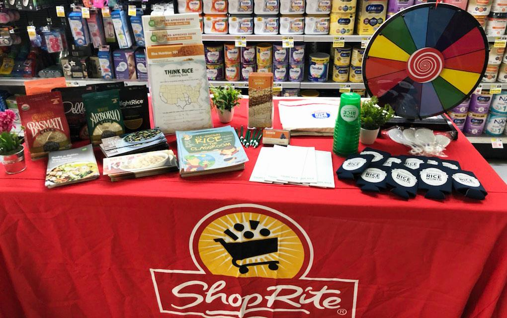 ShopRite demo table filled with bags of rice, coloring books, cups, brouchures, and game wheel