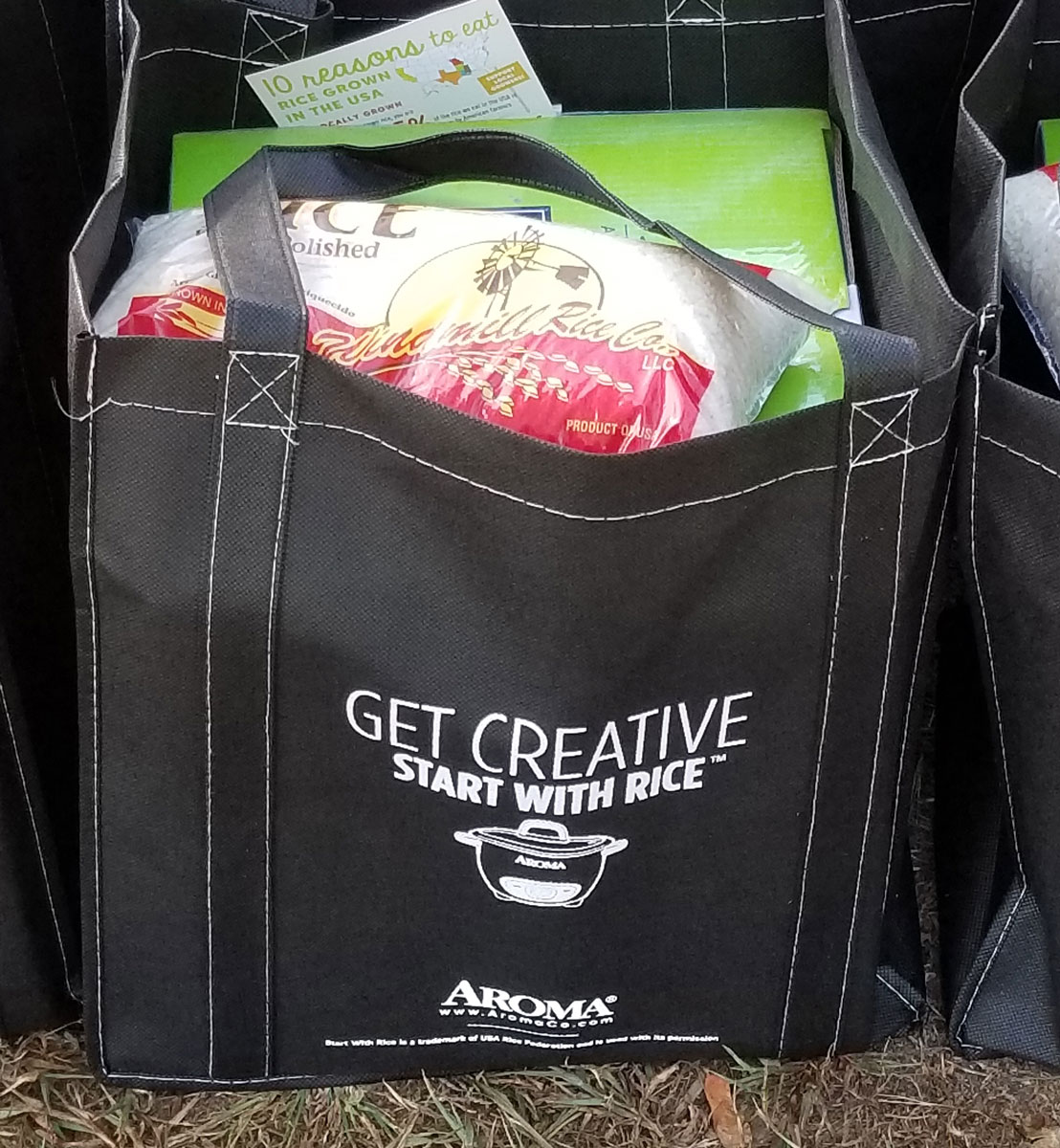 "Black shopping bag filled with green box and bag of rice, text on side says ""Get Creative, Start with Rice"""