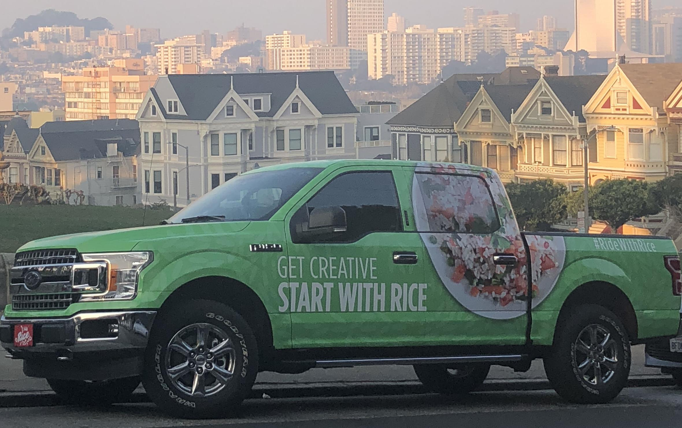 """Green Rice Truck covered with images of rice and text """"Get Creative, Start with Rice,"""" parked on street in front of Painted Ladies, colorful row houses in San Francisco"""