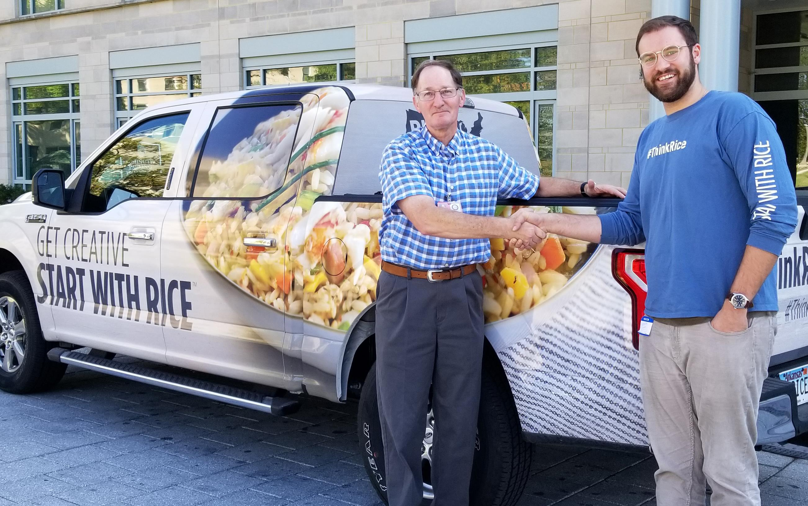 Two men shake hands while standing in front of pickup truck with rice messaging