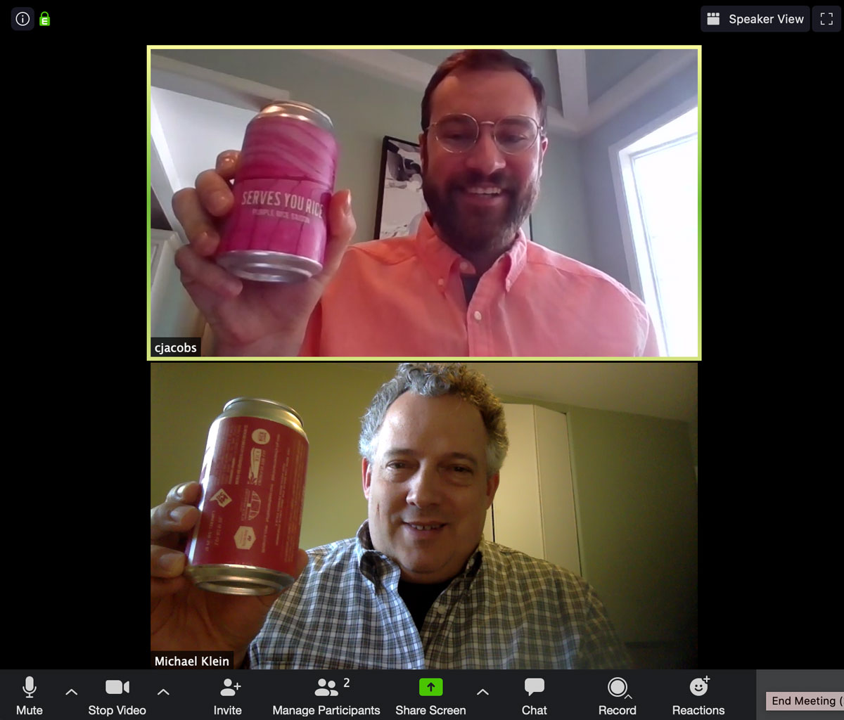 Two men celebrate virtual happy hour with bright pink cans of pink beer