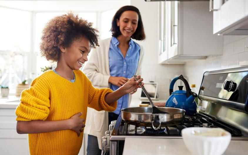 Young girl cooking on stove while mother looks on
