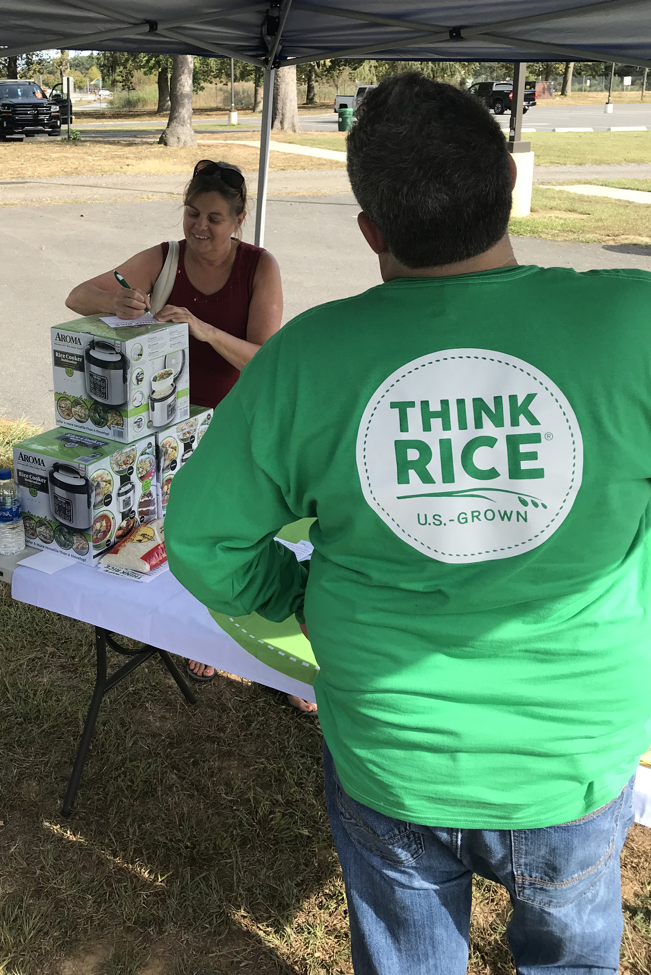Woman stands at table, writing, next to man wearing green Think Rice shirt with his back to the camera