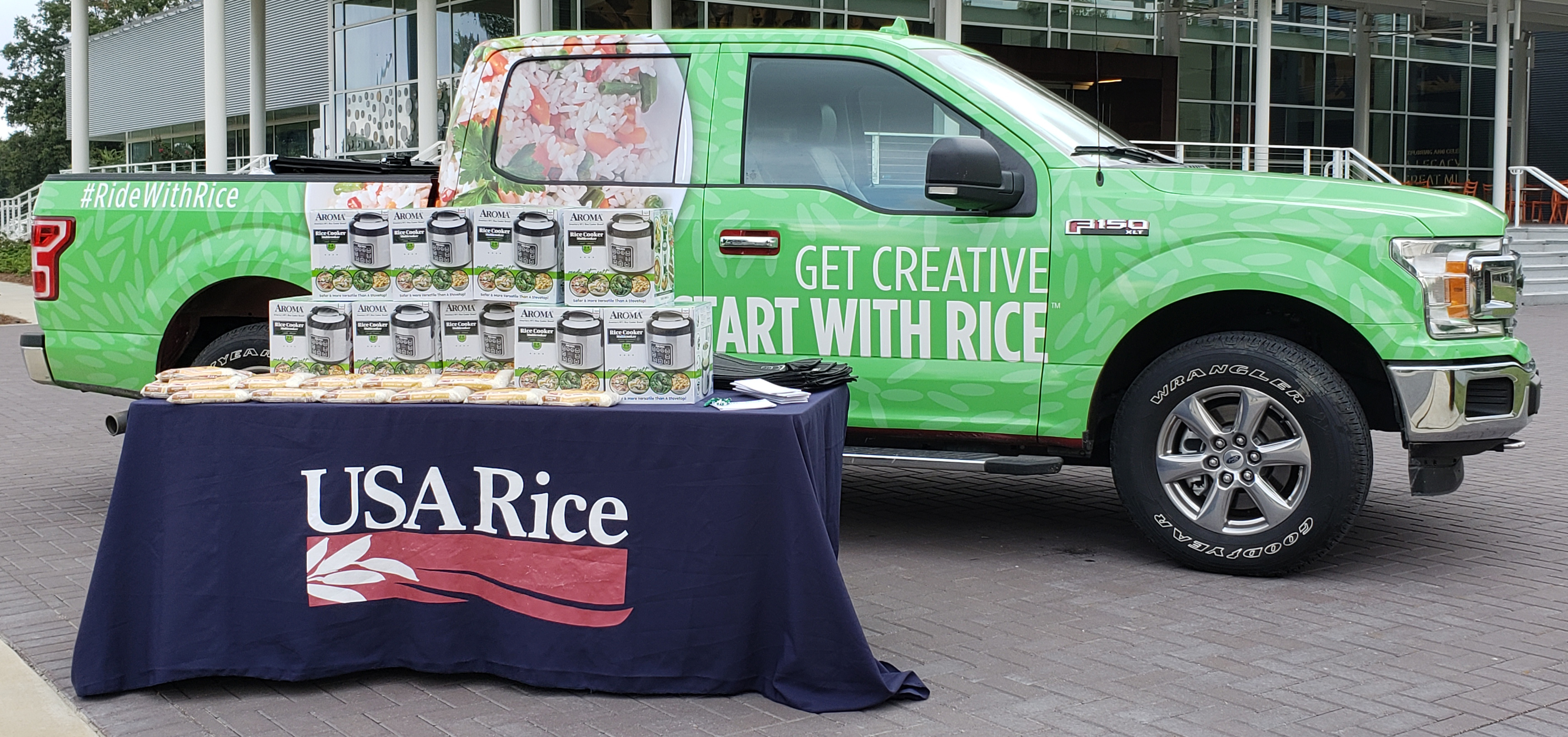 "Green pickup truck with designs & words ""Get Creative, Start With Rice,"" sits behind table with USA Rice banner and stacks of boxes on top"