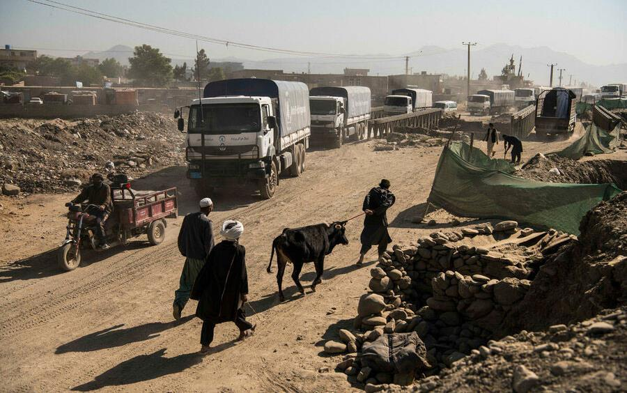 Truck convoy-on the road in-Kabul, Afghanistan, other vehicles, including motorcycle carts, and people walking with livestock crowd the street