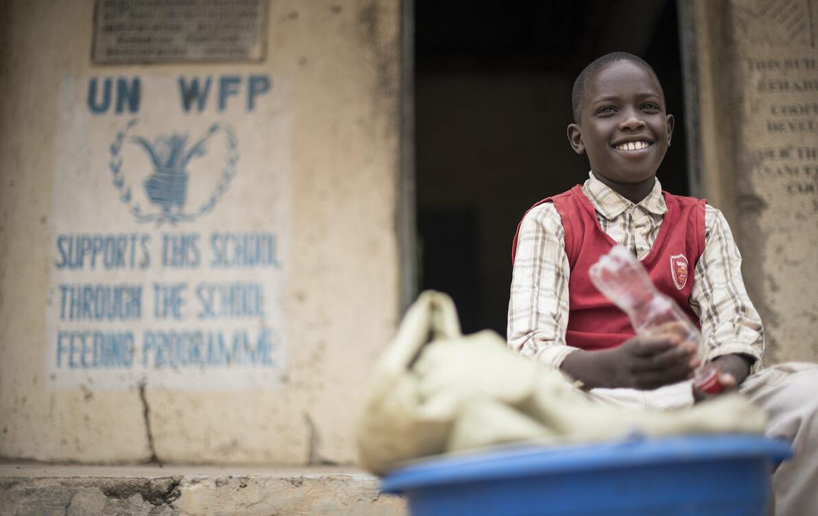 School boy sits in front of WFP signage
