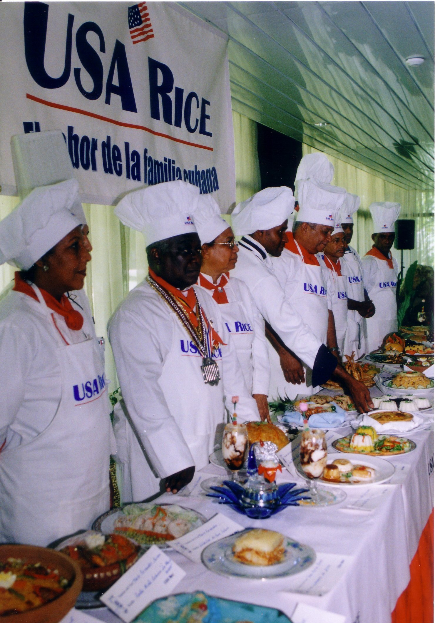 Long line of chefs wearing toques stand behind table laden with food, USA Rice banner hangs above their heads