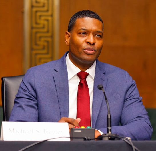 Black man wearing business suit sits at table, speaking into microphone, AgriPulse-photo