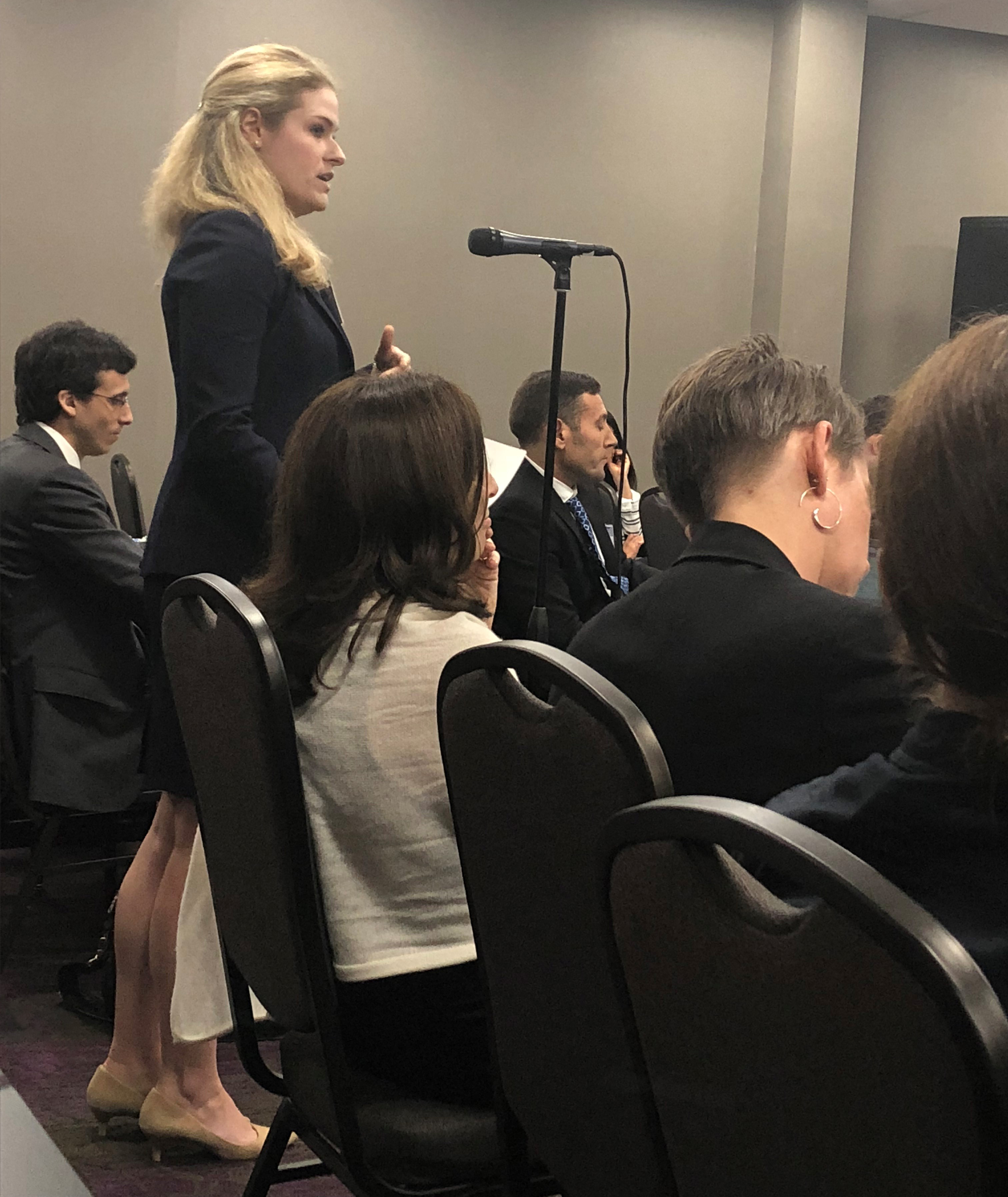 FDA Public Mtg, Lydia Holmes, wearing a dark business suit, stands in crowded conference room, talking into a standing microphone