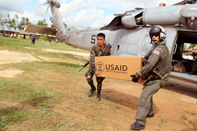 "Two men carry large box labeled ""USAID from the American People"" from a helicopter"