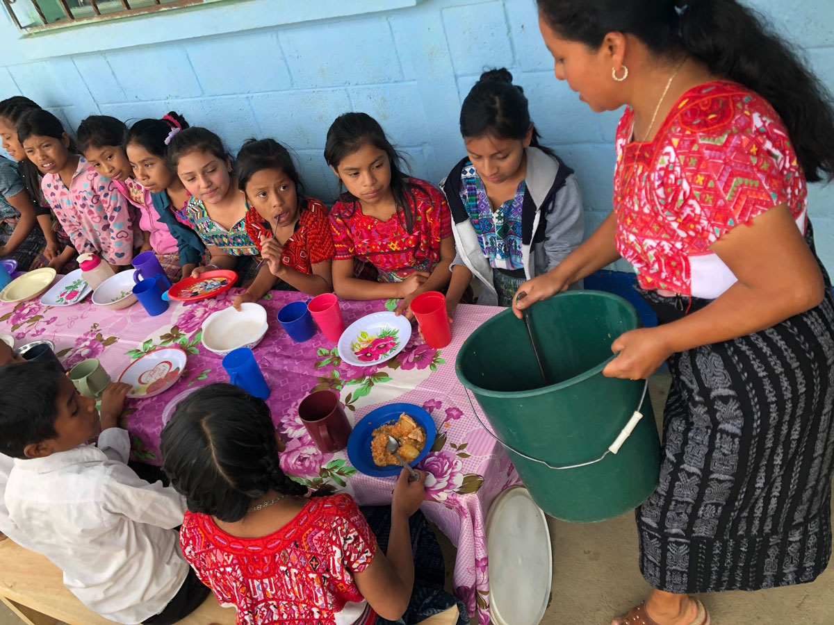 Children sit at a table, woman prepares to dish out food from a green bucket, everyone is colorfully dressed
