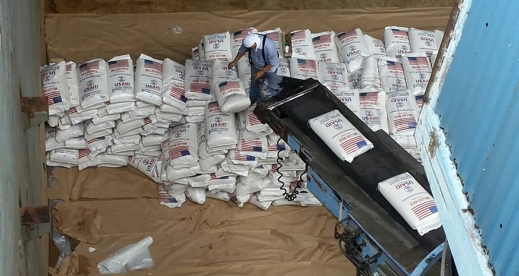 Bags of US rice in white bags with US flag on conveyer belt, being loaded into shipping container